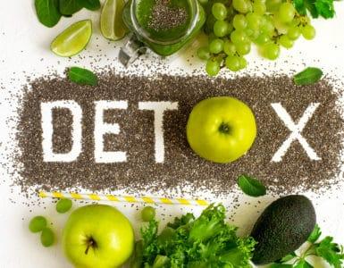 Tischplatte in der Mitte steht das Wort DETOX, darüber und darunter grünes Gemüse und Obst