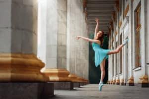 Ballerina macht eine Arabesque in einem antiken Gebäude