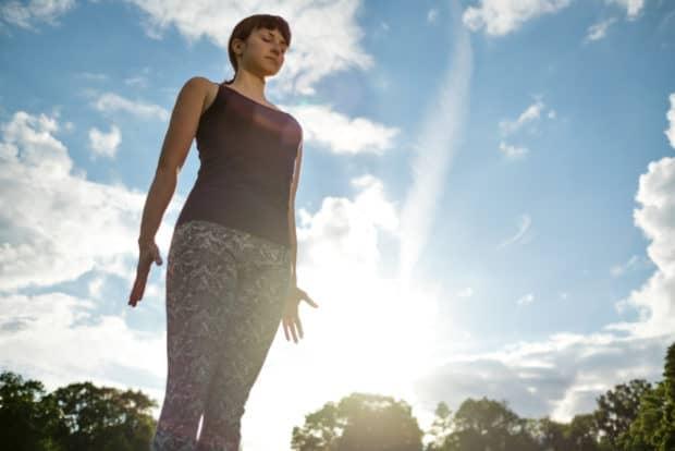 Junge Frau in Sportkleidung steht aufrecht und gerade