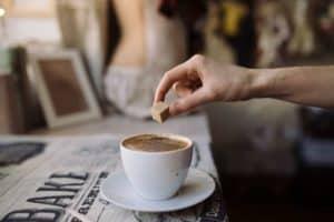 Hand einer jungen Frau wirft einen Würfelzucker in eine Kaffeetasse mit Capuccino