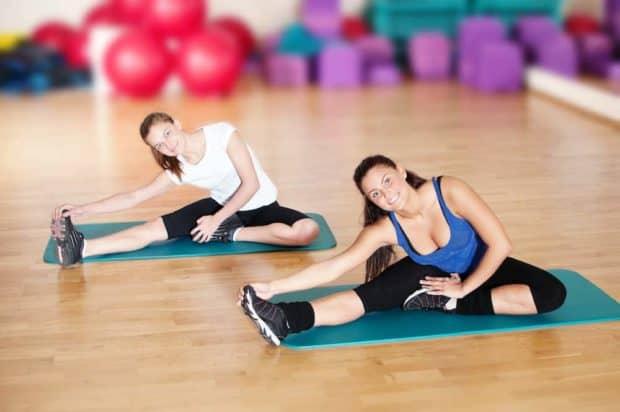 2 Frauen im Kursraum eines Fitnessstudios machen Übungen für jeden Figurtyp