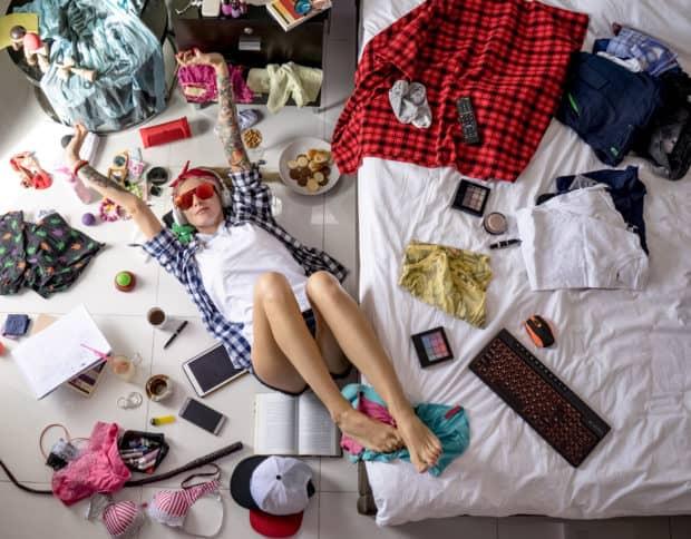 Junge Frau liegt in einem unaufgeräumtem chaotischen Zimmer