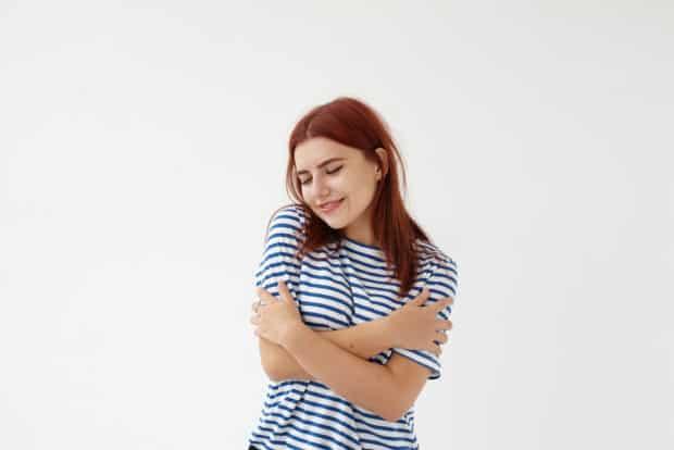 Junge Frau mit gestreiftem Shirt legt liebevoll die Arme um sich lelbst