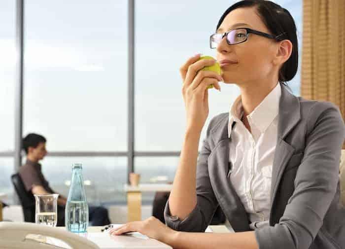 Frau isst gesund am Arbeitsplatz