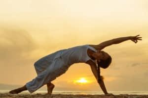 Frau macht Yoga am Meer auf Bali im Sonnenuntergang