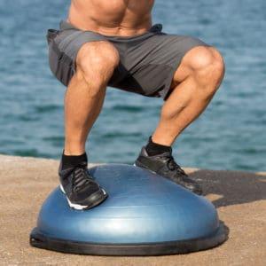 Mann mit schwarzen Turnschuhen steht auf Wackelball und macht Squats