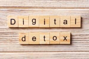 Holzhintergrund darauf Würfel mit Buchstaben die die Worte digital Detox ergeben