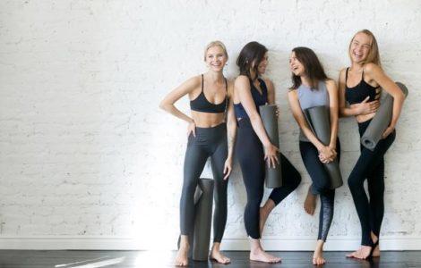 Vier Frauen in Sportkleidung lehnen an Wand und lachen