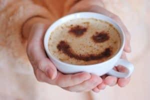 Hände einer Frau halten Kaffee-Tasse mit Milchkaffee auf dem Schaum ist ein Smiley mit Kakaopulver gestreut