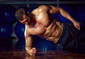 Muskulöser Mann mit freiem Oberkörper bei der Ausführung von Side Planks