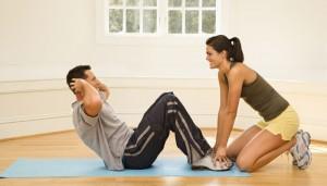 Ein Mann macht Sit Ups, während eine Frau seine Füße auf dem Boden hält