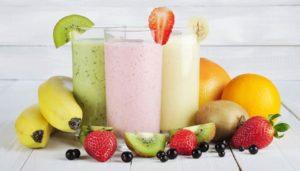 3 Gläser gefüllt mit Kiwi-, Erdbeer- und Bananen-Smoothie umringt von Obst