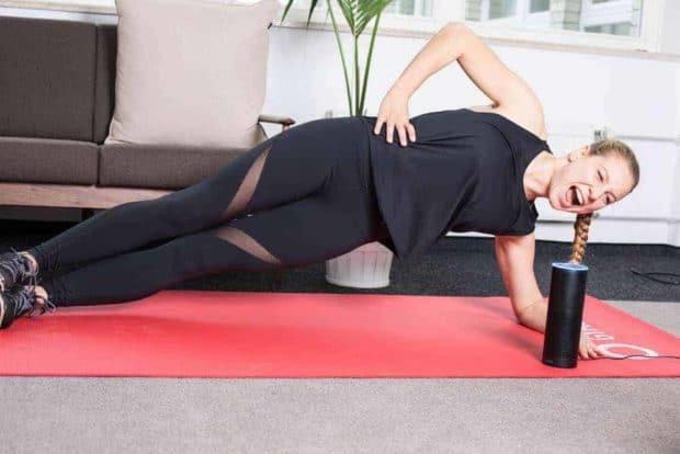 Junge Frau trainiert auf roter Trainingsmatte mit dem GYMONDO Alexa Skill