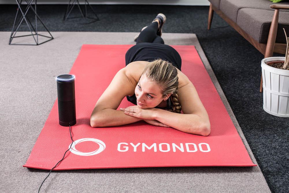 Frau in Sportkleidung liegt auf roter Trainingsmatte und ruht sich aus nach dem Workout mit dem Gymondo Alexa Skill