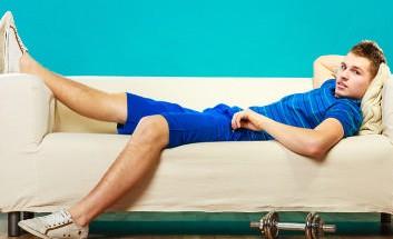 Mann auf Sofa Faul Hantel im Vordergrund