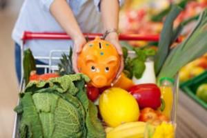 Frau legt Sparschwein in einen Einkaufswagen voller Gemüse