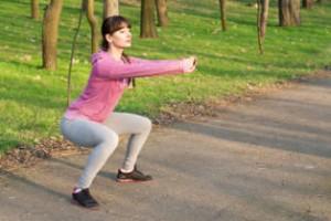 Frau im Park bei der Ausführung der Fitnessübung Squats
