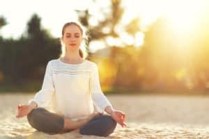 Frau sitzt entspannt draußen und meditiert
