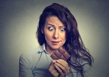 Gestresste Frau schaut auf ein Stück Schokolade.