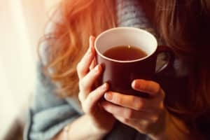 Frau hält Tasse mit heißem Tee in den Händen