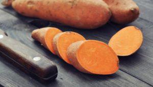Zwei Süßkartoffeln neben drei Süßkartoffelscheiben auf einem Holztisch