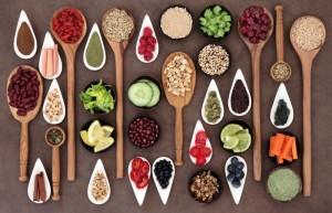 Superfoods-Gewürze, -körner, -beeren und -samen auf Löffeln und in Keramikschalen portioniert