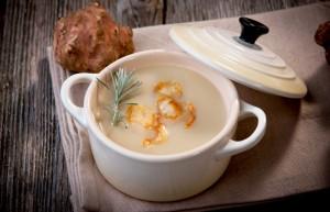 Suppe mit Topinambur in weißer Keramikschüssel