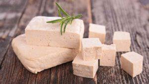 Tofu, gewürfelt und in Scheiben auf einem Holztisch, garniert mit einem grünen Zweig