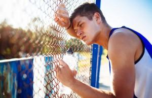 Mann lehnt nach anstrengendem Training bei hohen Temperaturen an einem Maschendrahtzaun