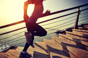 Frau in Sportkleidung rennt Treppe hoch