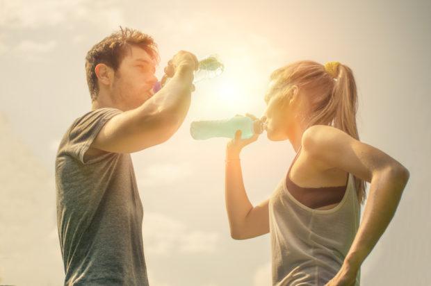 Frau und Mann stehen sich gegenüber und trinken Wasser