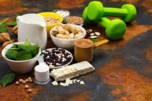 Vegane Lebensmittel und Kurzhanteln auf Tisch