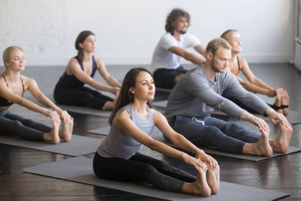 Gruppe von Männern und Frauen machen Yoga für Sportler - die Vorbeuge