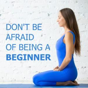 Junge Frau in blauem Sporttrikot macht Yoga neben ihr ein Schriftzug: Keine Angst ein Anfänger zu sein