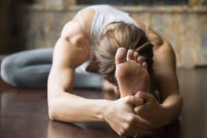 Junge Frau auf Yogamatte macht eine Vorbeuge
