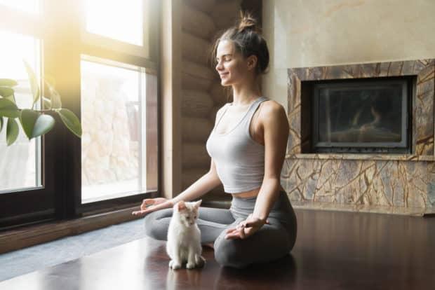 Junge Frau sitzt auf Yogamatte im Lotussitz daneben eine kleine Katze