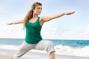 Frau am Strand macht Yoga-Übung