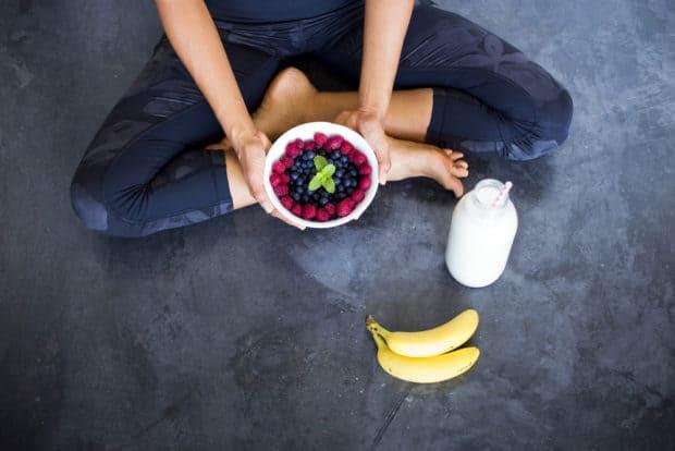 Frau im Lotussitz hält Schale mit frischen Früchten in den Händen